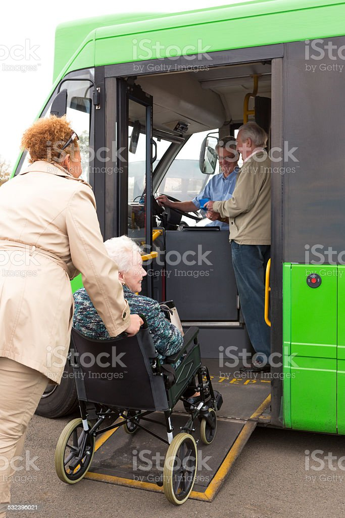Carer Pushing Senior Woman onto Bus Via Wheelchair Ramp stock photo