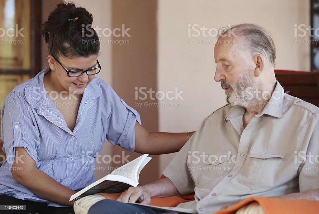 carer reading to senior royalty-free stock photo
