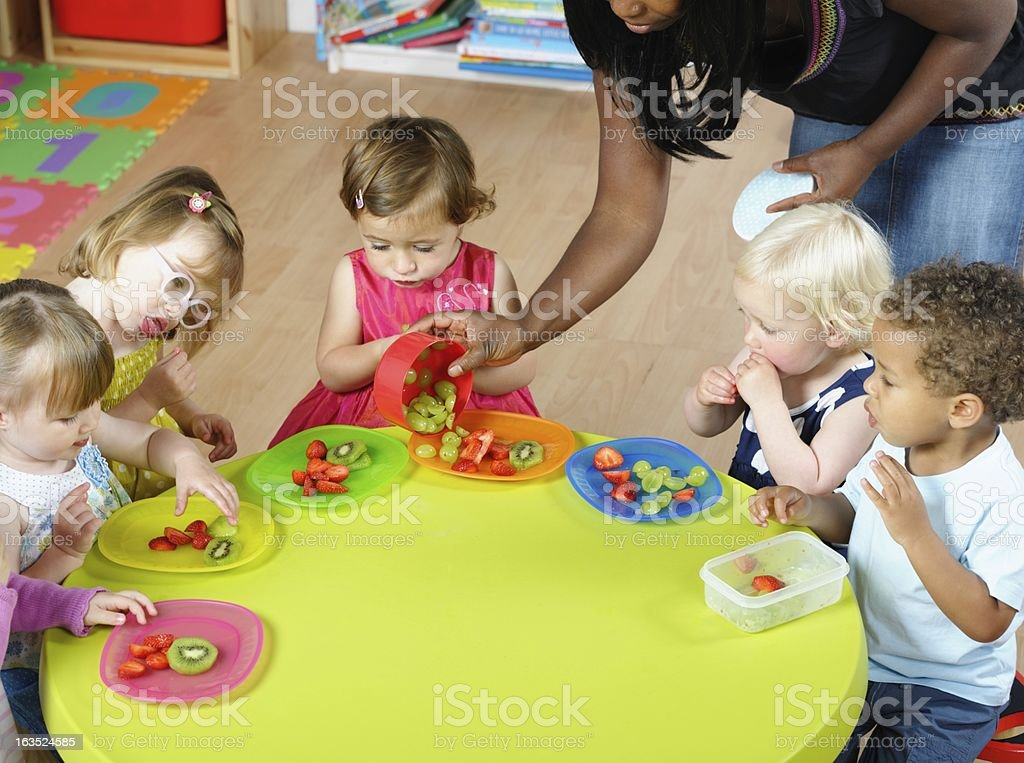 Carer Serving Fruit To Group Of Toddlers/ Children At Nursery stock photo
