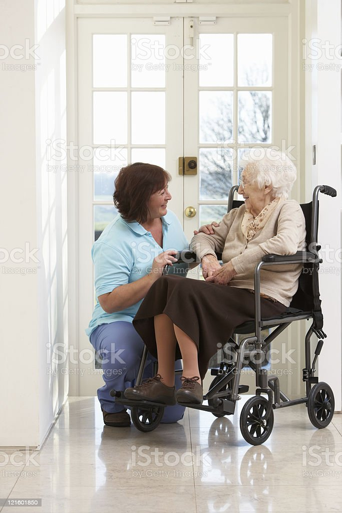Carer With Disabled Senior Woman Sitting In Wheelchair stock photo