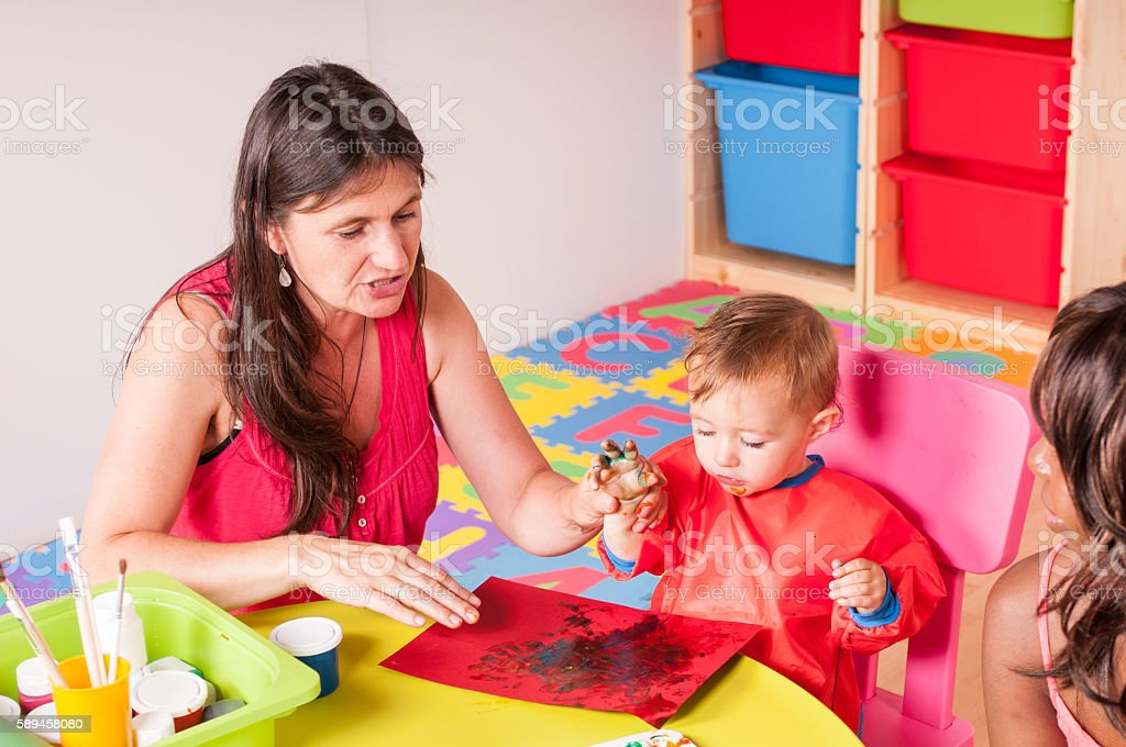 Carers And Babies/ Toddlers Doing Finger Painting stock photo