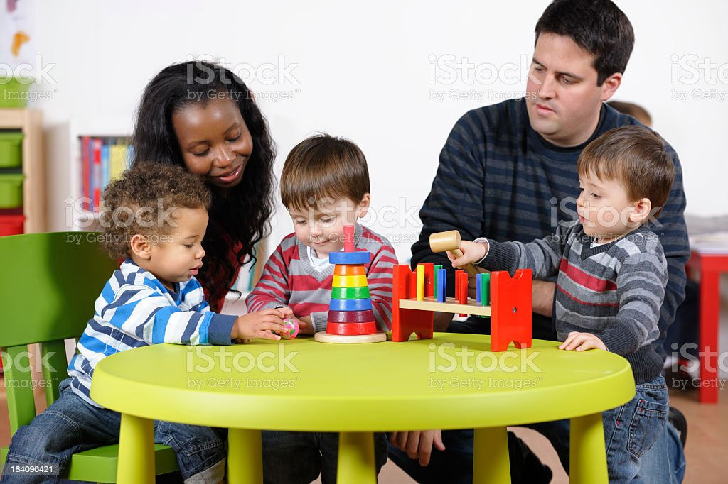 Carers Supervising Group Of Toddlers Using Developmental Toy At Playtime stock photo