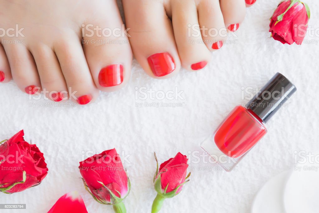 Cares about woman\'s foot nails. Pedicure beauty salon. Red nail...