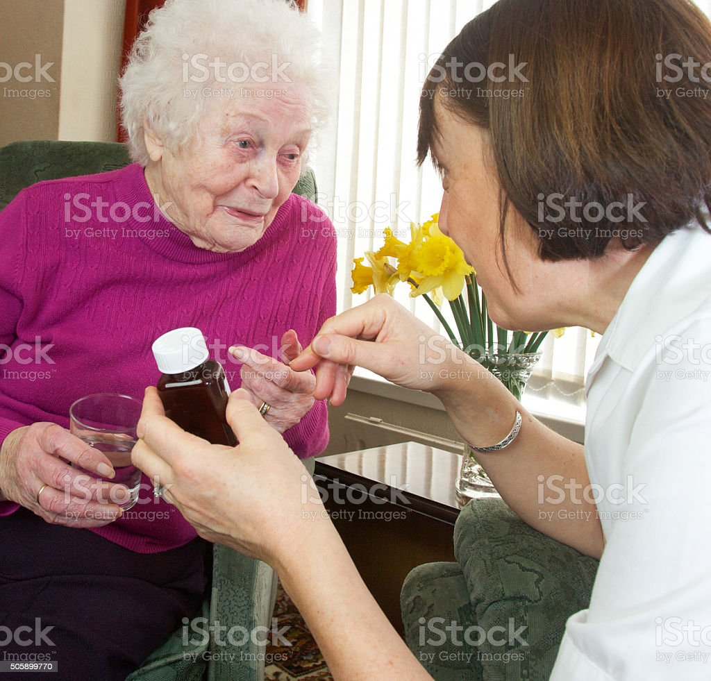 Careworker nurse assists an elderly female client with medicines. stock photo