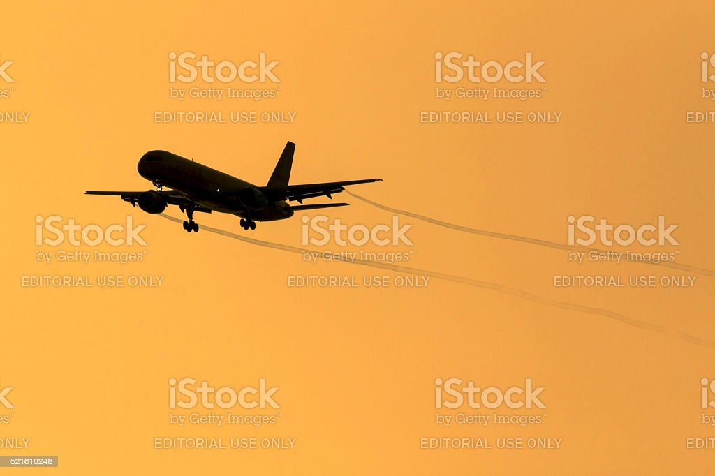 Cargo 757 with vapour trails an orange sunrise stock photo