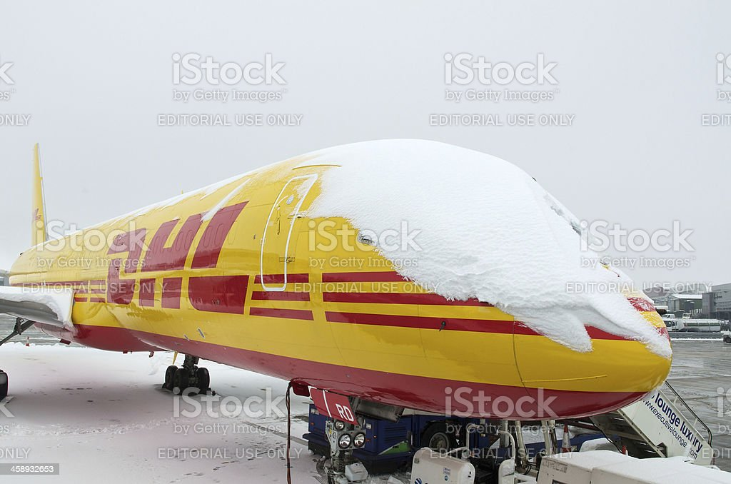 DHL Cargo aircraft covered in snow under cloudy skies stock photo
