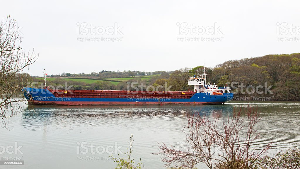 Cargo boat negotiating a narrow passage stock photo