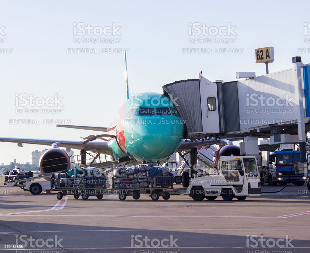 Cargo cars carrying passenger's baggages to airplane stock photo