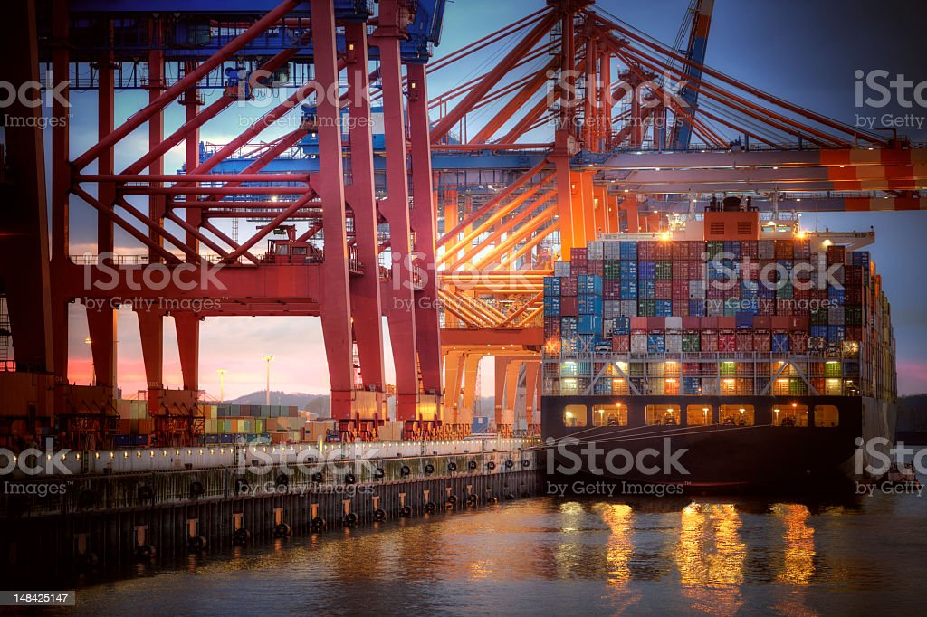 Cargo container docked in colorful harbor stock photo