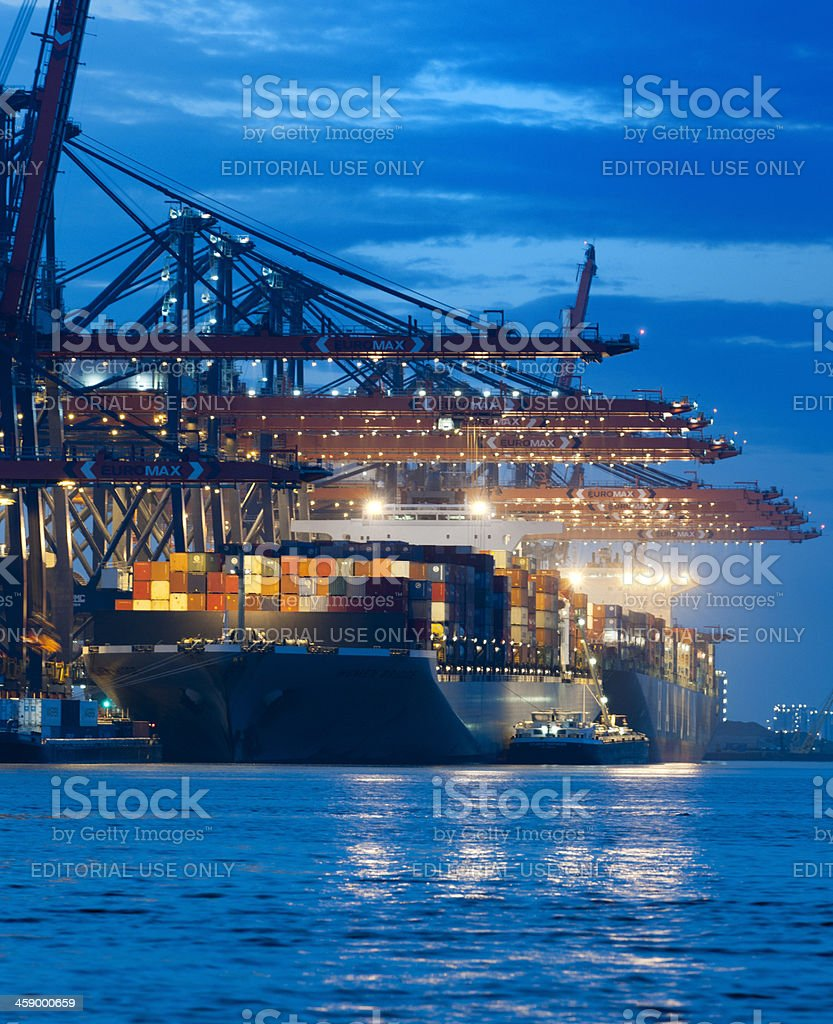 cargo container ship in commercial dock at night stock photo