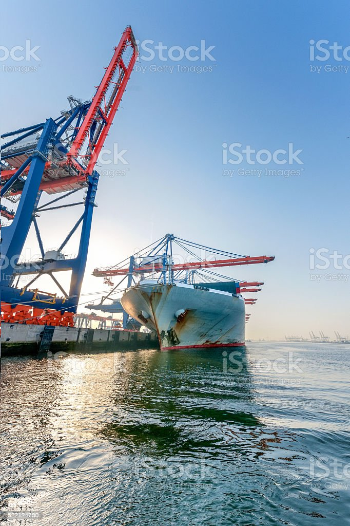 cargo container ship loading in harbour, sunrise stock photo