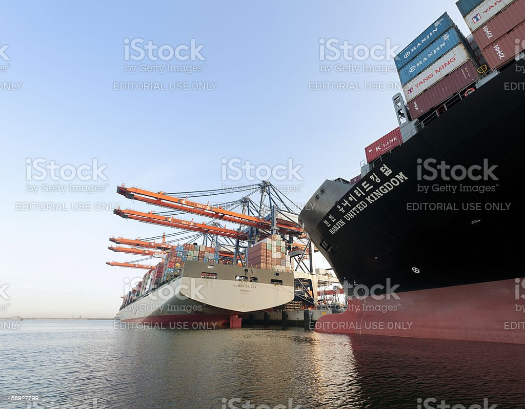 cargo container ships loading in harbour at sunrise stock photo