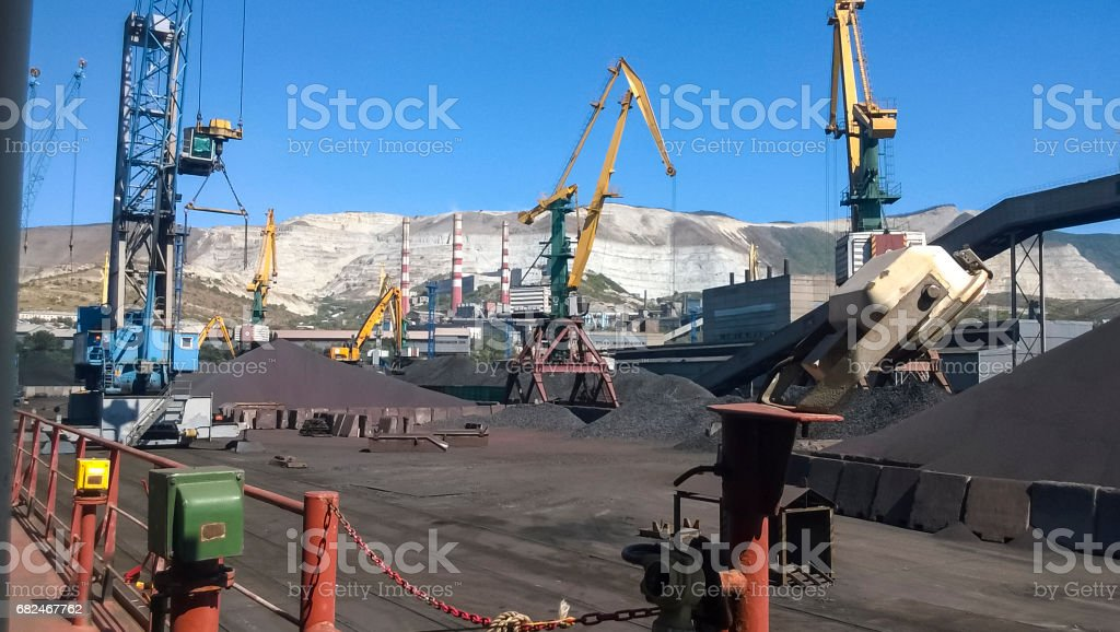 Cargo industrial port, port cranes. Loading of anthracite. Transportation of coal. Heap of coal stock photo