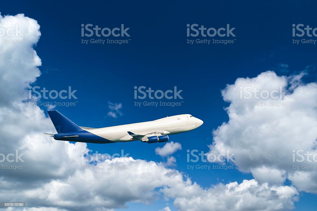Cargo jet in flight against fluffy clouds and blue sky stock photo