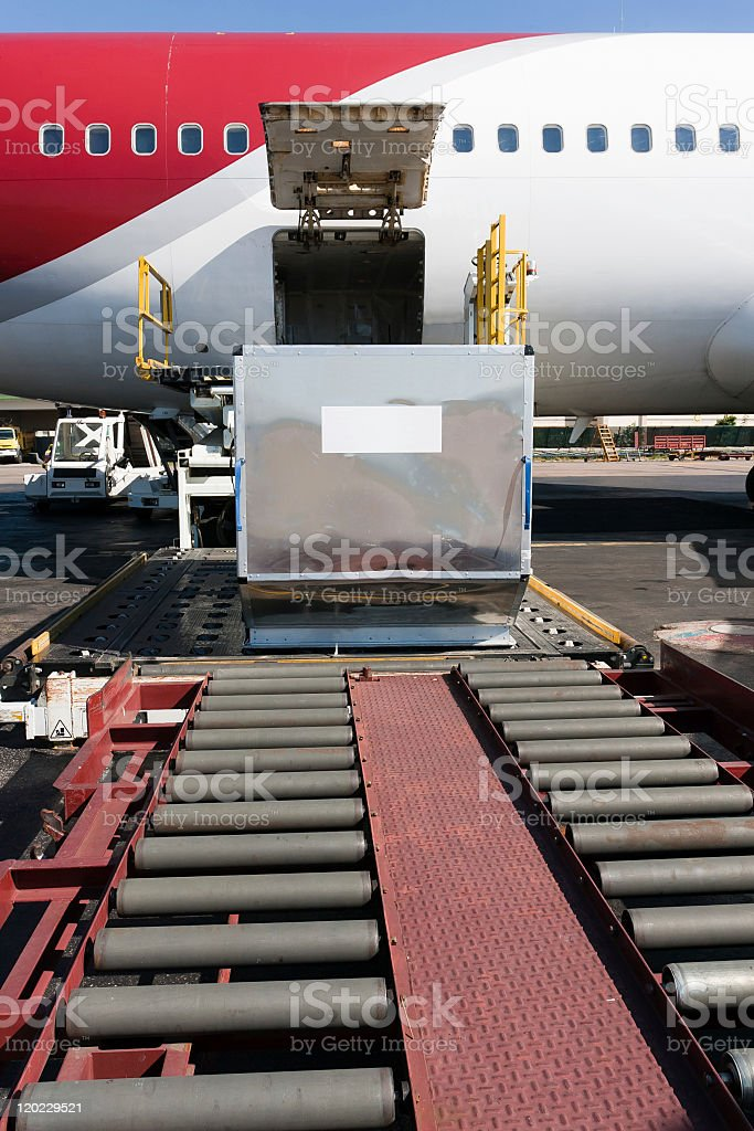 Cargo plane being loaded by conveyor belt royalty-free stock photo