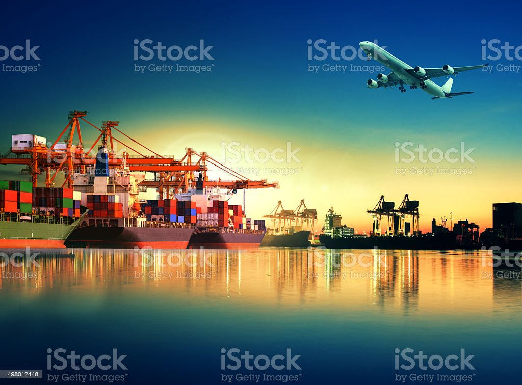cargo plane flying over ship in port stock photo
