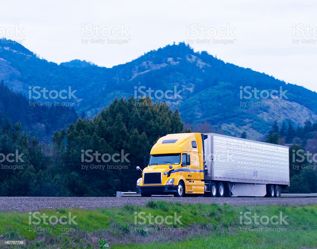 Cargo semi truck reefer trailer yellow green highway winding stock photo