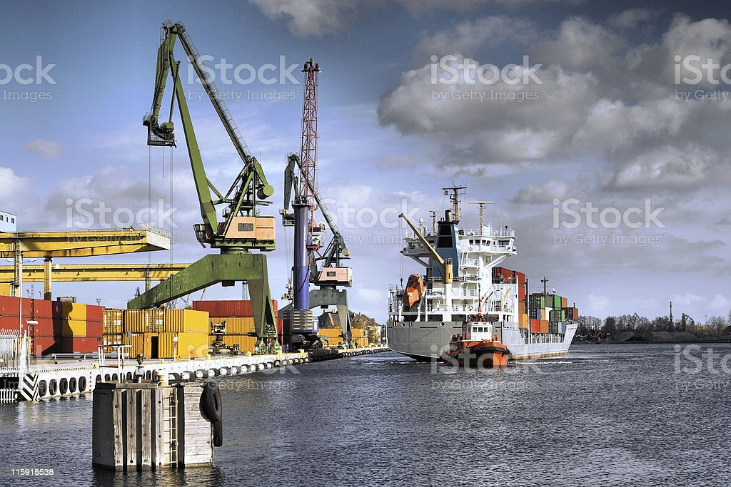 A cargo ship and cranes in a shipyard royalty-free stock photo