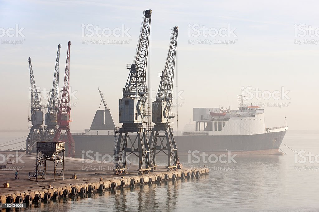 Cargo ship and port cranes stock photo