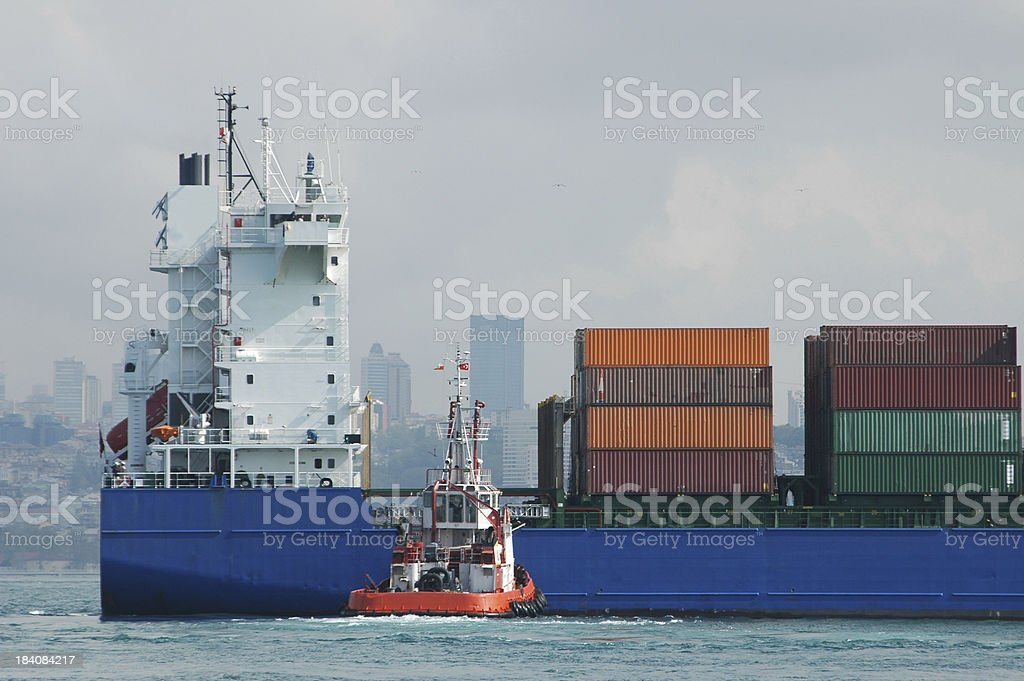 Cargo ship and tugboat royalty-free stock photo