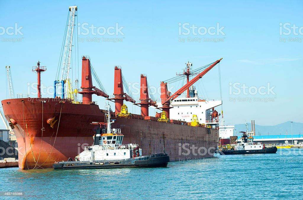 Cargo ship and tugboat stock photo