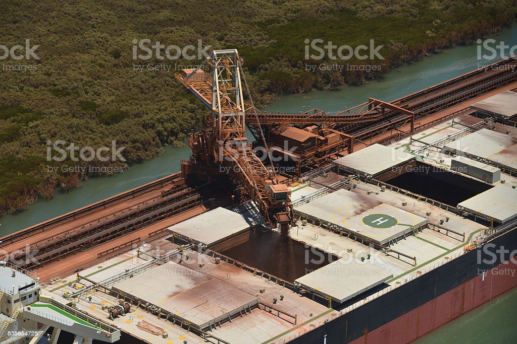 Cargo ship being loaded with crushed ore. stock photo