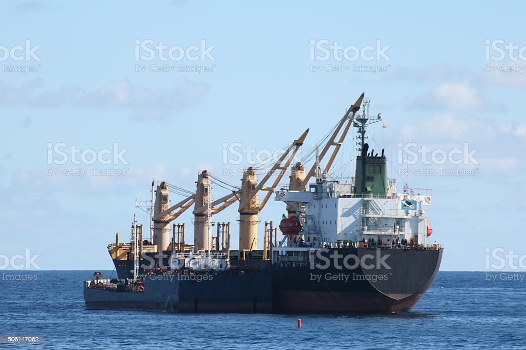 Cargo ship being refuelled at sea stock photo
