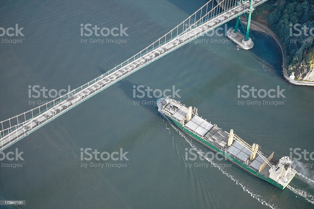 Cargo ship crossing under bridge stock photo