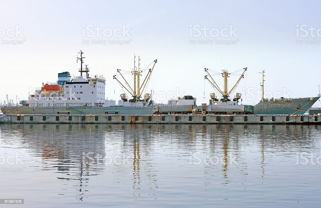 cargo ship docked port fully reflected in water royalty-free stock photo