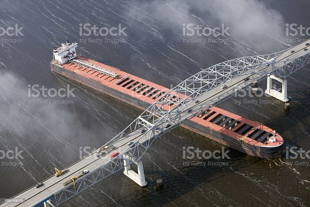 Cargo Ship Enters Port under Bridge Aerial stock photo