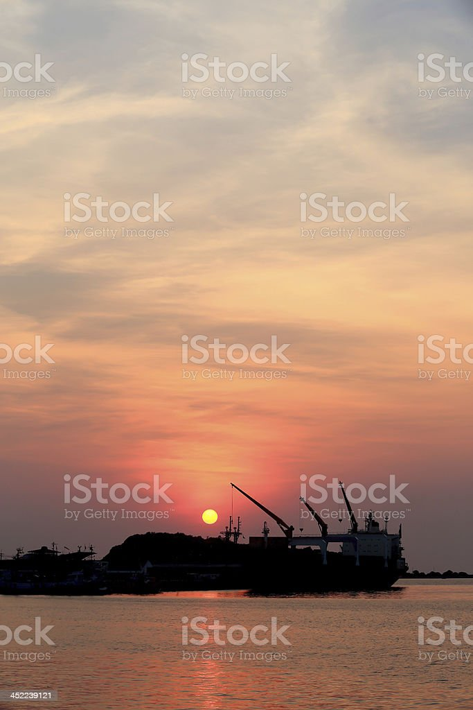 Cargo ship in the harbor at sunset royalty-free stock photo