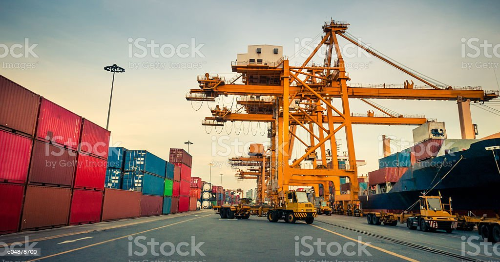 Cargo ship in the harbor at sunset . stock photo