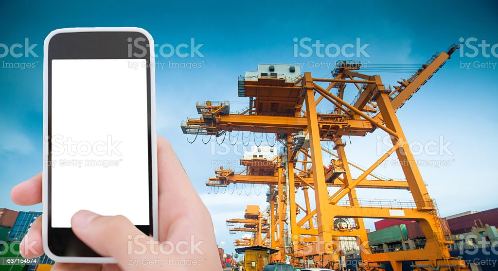 Cargo ship in the harbor at sunset  with smart phone stock photo