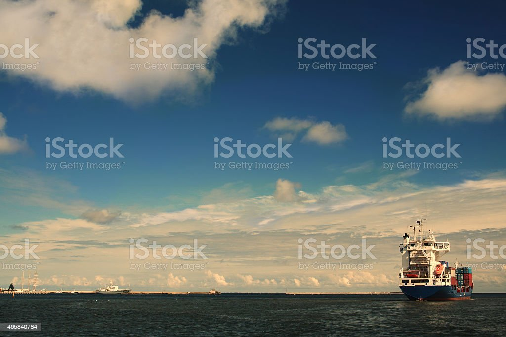 cargo ship leaving the port small stock photo