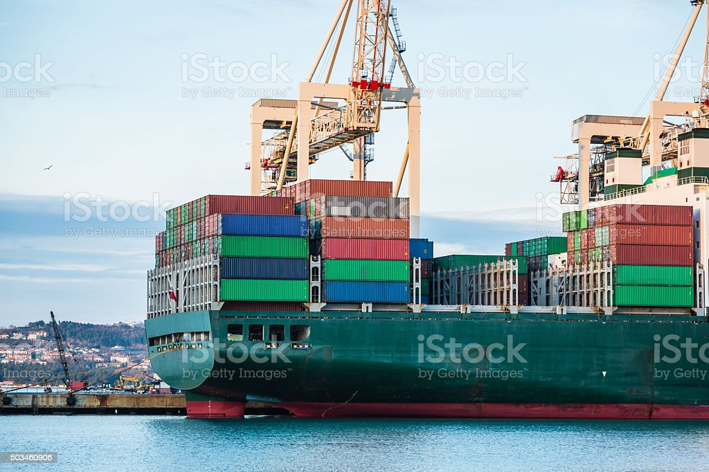 Cargo ship moored at container terminal in port stock photo