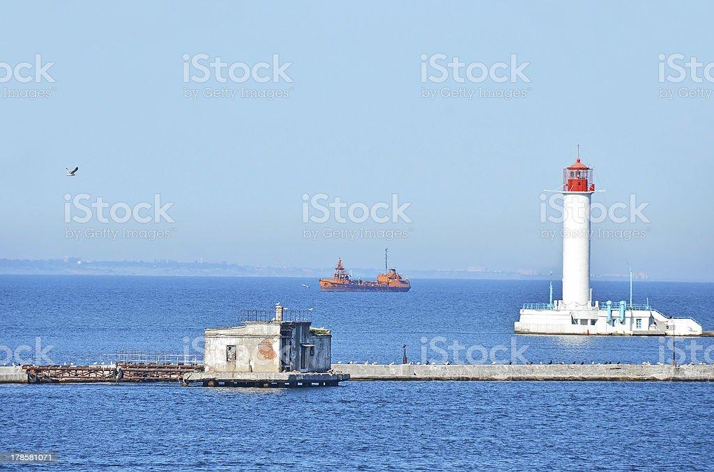 Cargo ship near lighthouse royalty-free stock photo