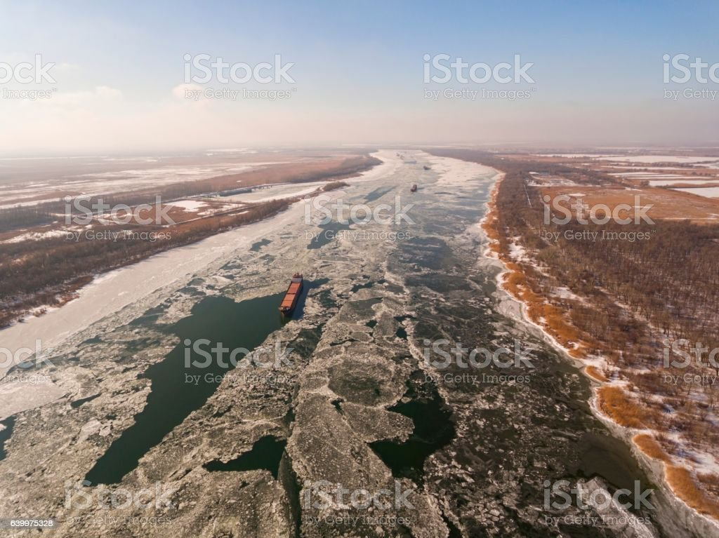 Cargo ship on the ice river in winter. stock photo