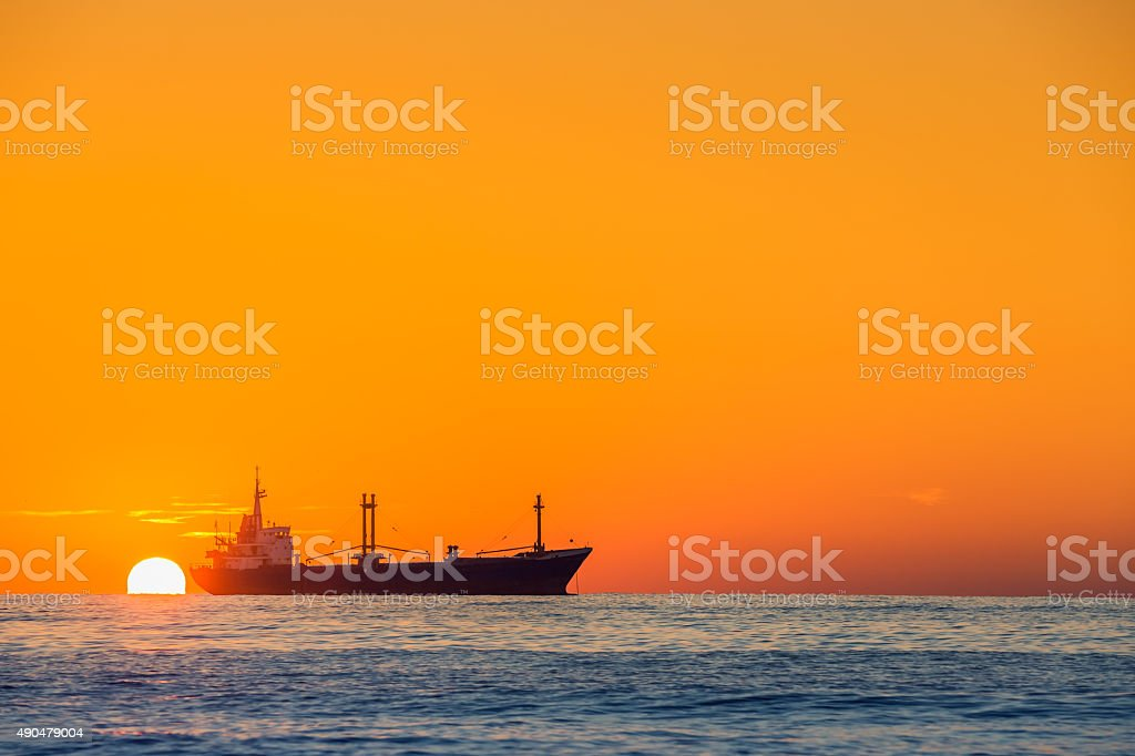 Cargo ship sailing on sunrise near the sea harbor stock photo