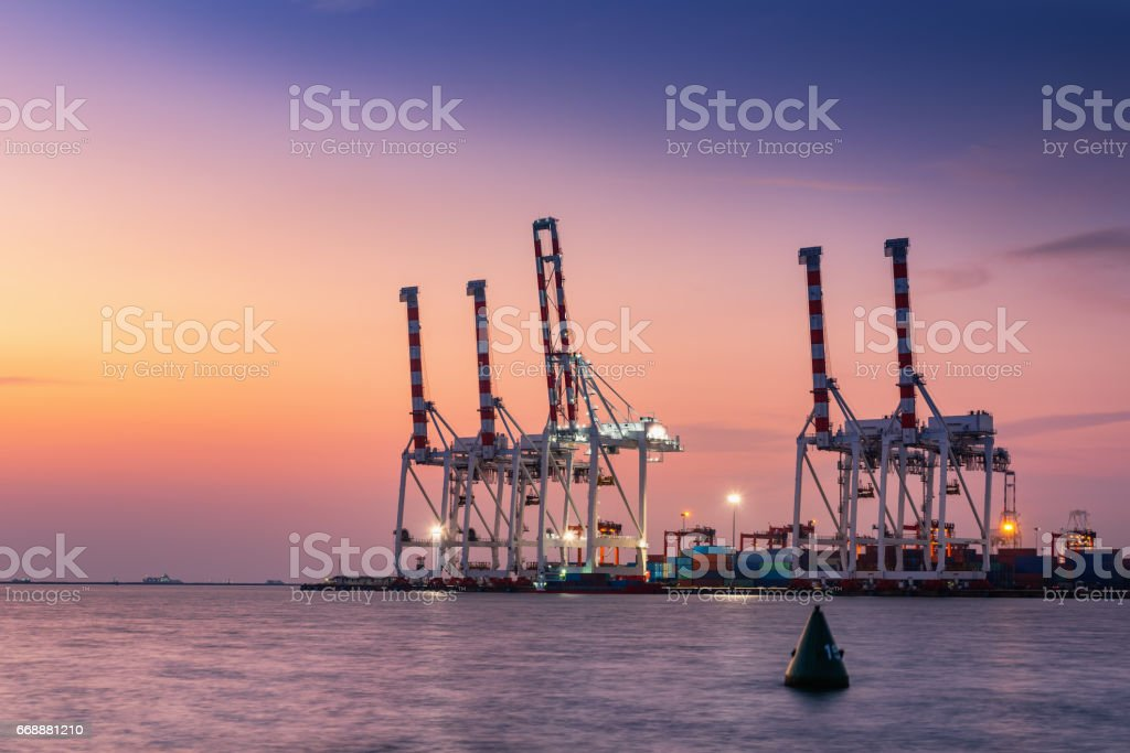 Cargo ship terminal at twilight scene, Unloading crane of cargo ship terminal, Sunset shot. stock photo