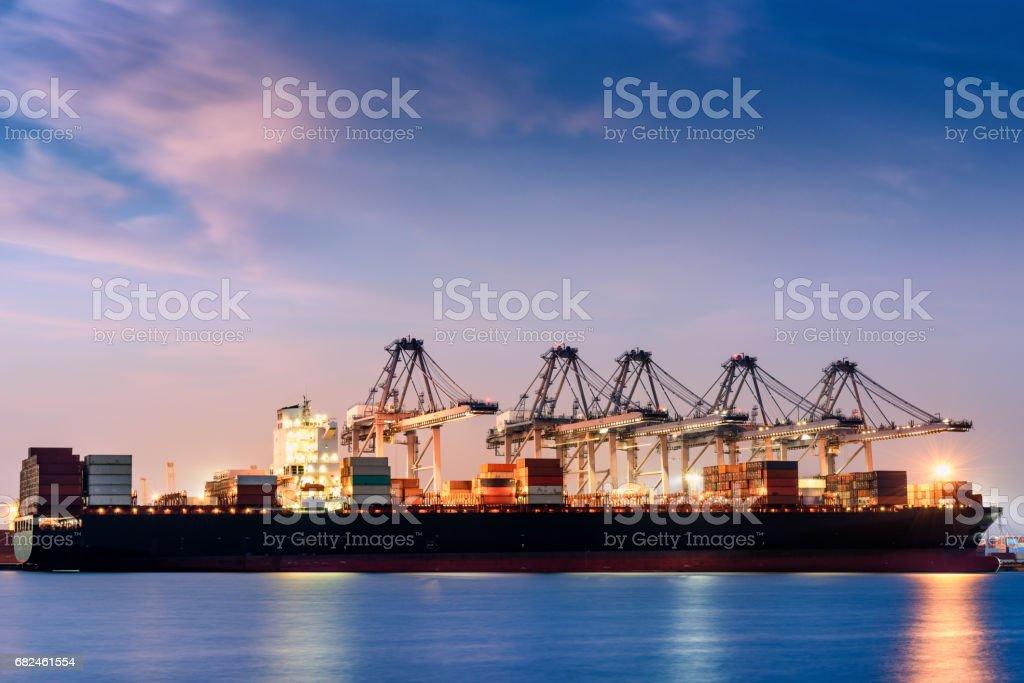 Cargo ship terminal unloading at twilight scene. stock photo