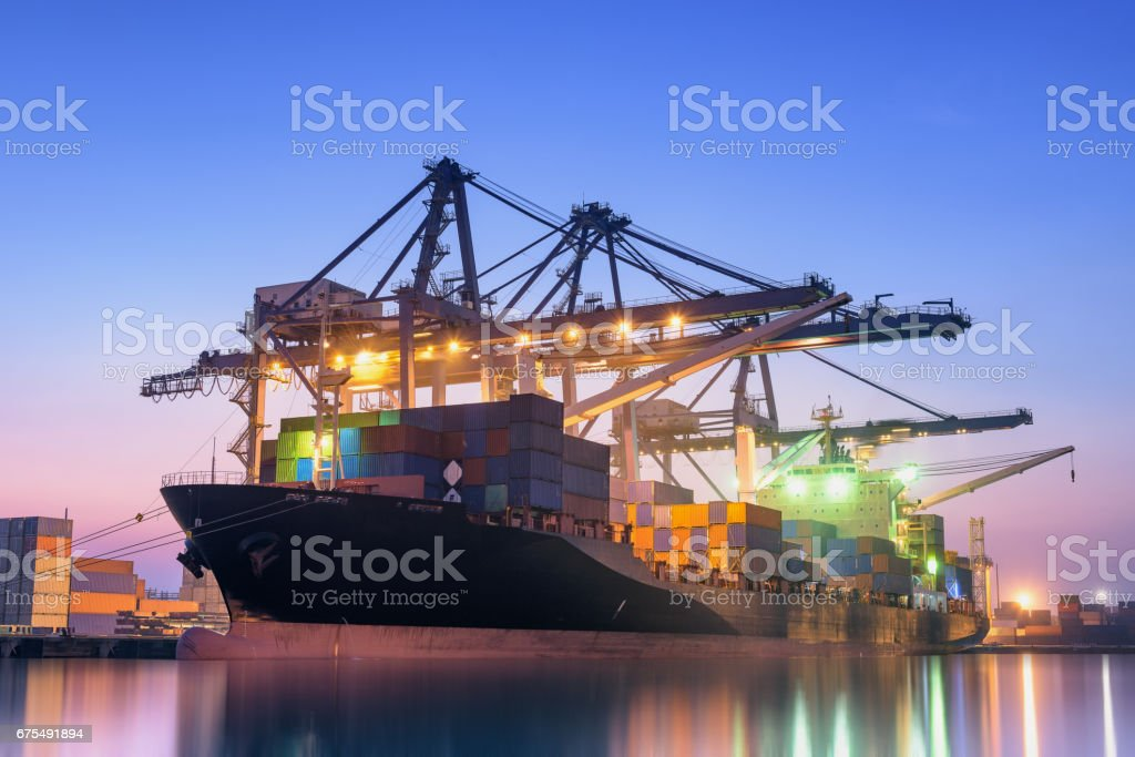 Cargo ship unloading container at twilight. stock photo