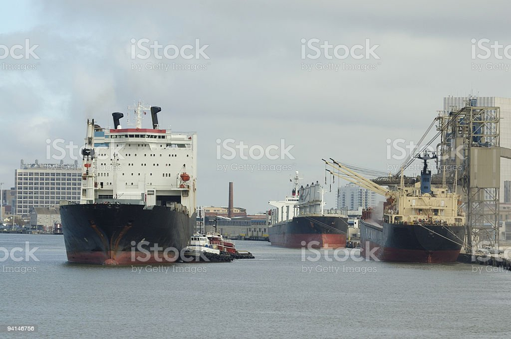 Cargo ships and tugboats at harbor. Industrial port. stock photo