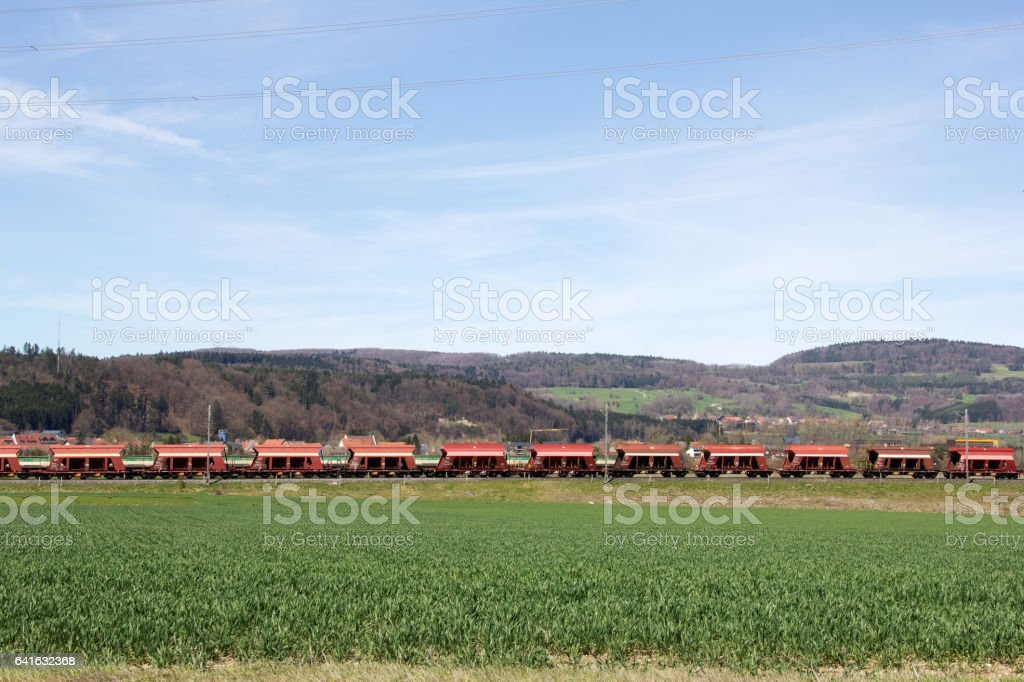 Cargo train crossing the field stock photo