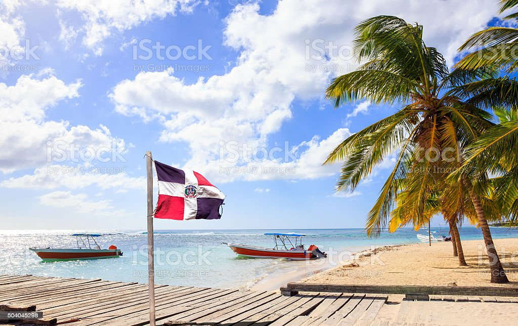 Caribbean beach and Dominican Republic flag stock photo