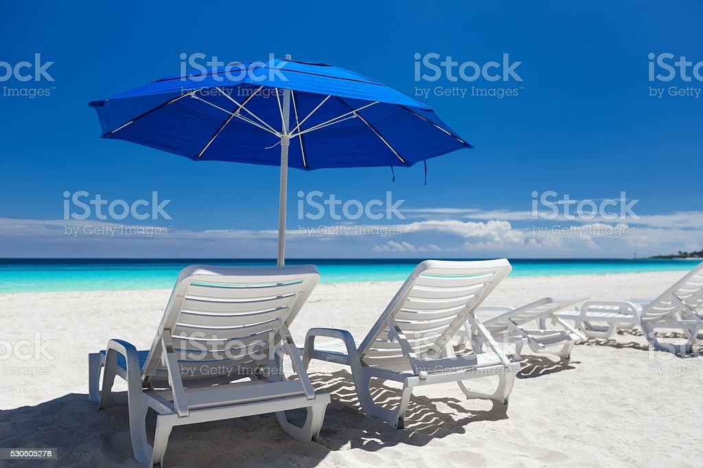 Caribbean beach with blue sun umbrellas and white beds stock photo