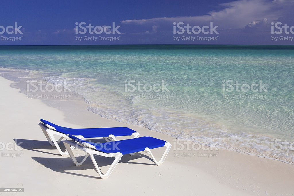 Caribbean beach with canvas chairs in Cuba stock photo