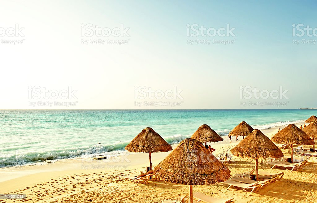 Caribbean beach with thatched umbrellas and sun loungers stock photo