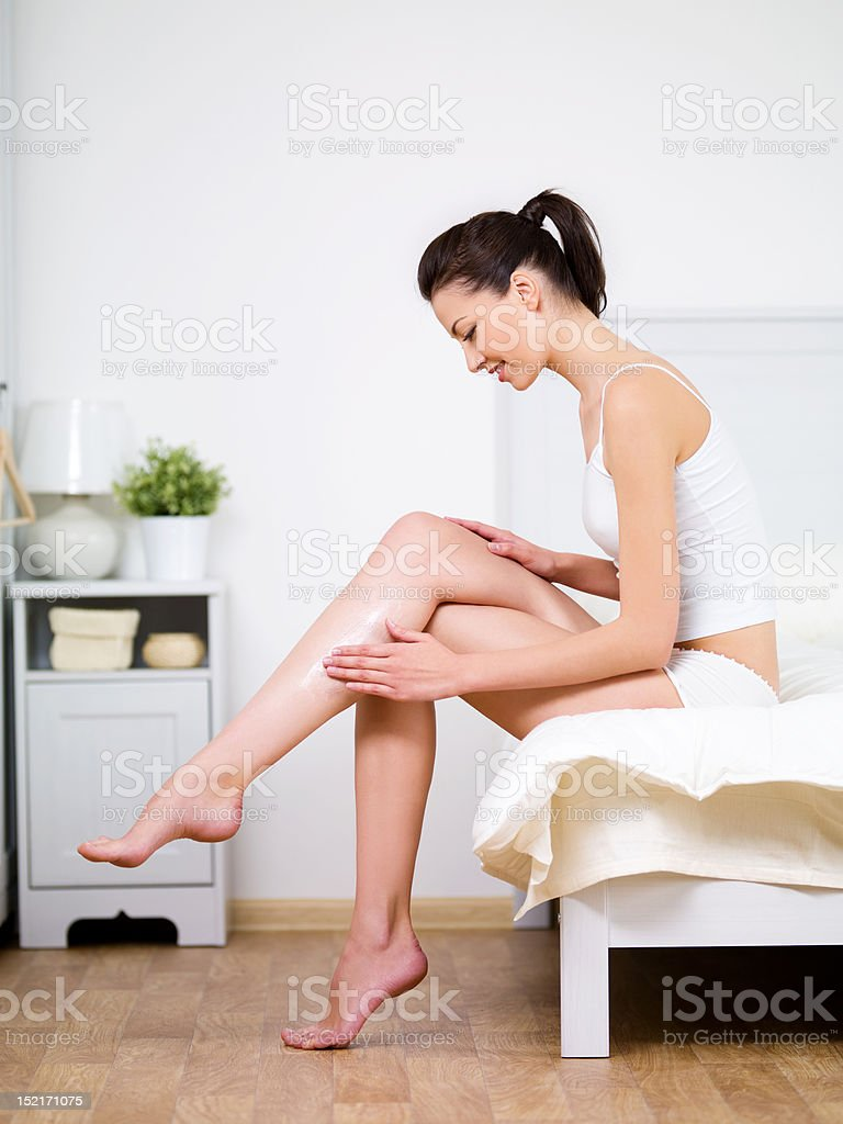 Caring about woman's leg with cream stock photo