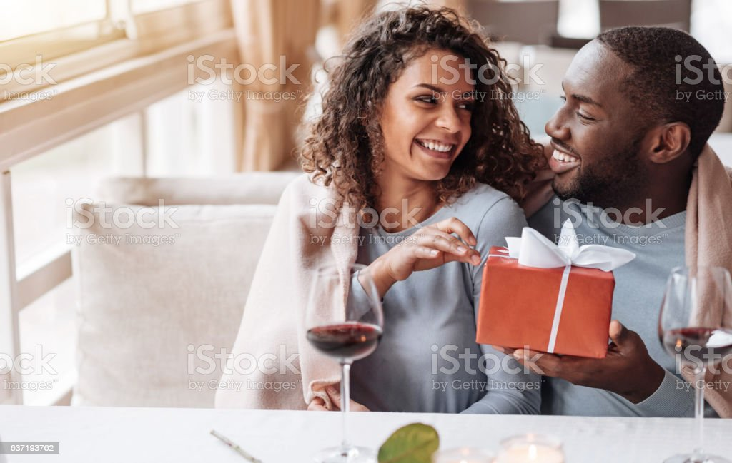 Caring African American man giving the present to his girlfriend stock photo
