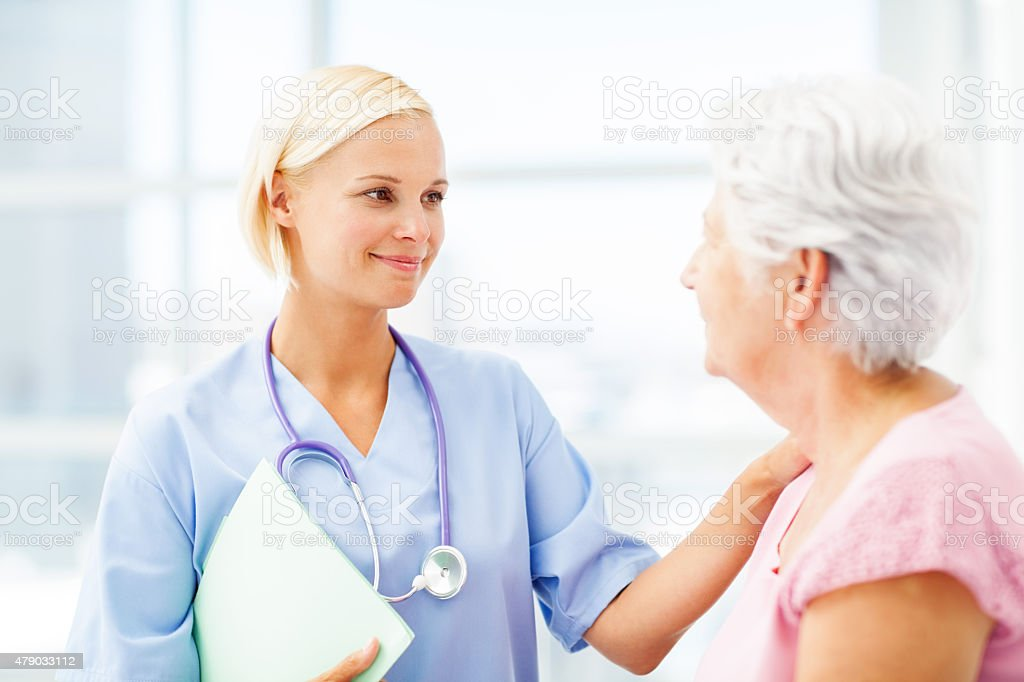 Caring Doctor Consoling Senior Patient In Hospital stock photo